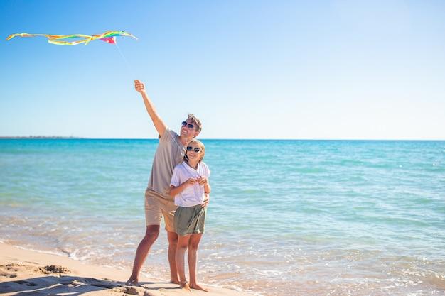Familie spielt mit einem drachen am strand