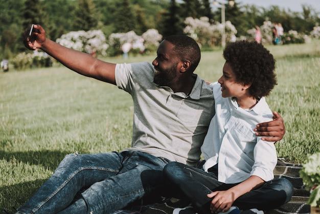 Familie umarmt sich und der vati, der selfie macht.