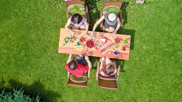 Familie und freunde, die zusammen draußen auf sommergartenparty essen. luftaufnahme des tisches mit essen und getränken von oben. freizeit-, ferien- und picknickkonzept