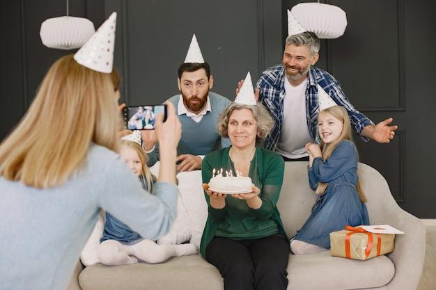 Familie und ihre zwei töchter feiern geburtstagzwei männer und zwei kleine mädchen sitzen auf einem sofa mutter macht ein foto von ihnen