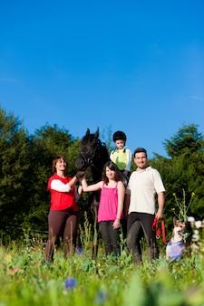 Familie und kinder posieren mit pferd