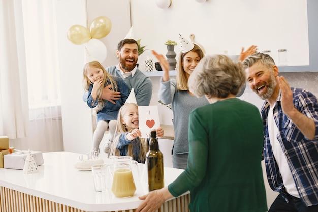 Familie und zwei ihre töchter feiern den geburtstag der großmütter die leute applaudieren und lächeln