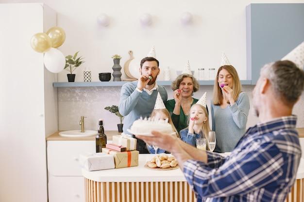 Familie und zwei ihre töchter feiern den geburtstag der großmütter erwachsener sohn hält kuchen mit kerzen