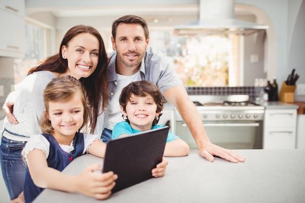 Familie unter verwendung der digitalen tablette bei bei tisch stehen