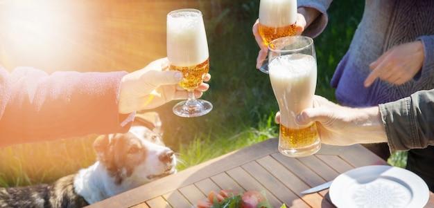 Familie unterschiedlichen alters feiern fröhlich im freien mit biergläsern und verkünden toast. menschen und hund beim abendessen in einem hausgarten im sommersonnenlicht