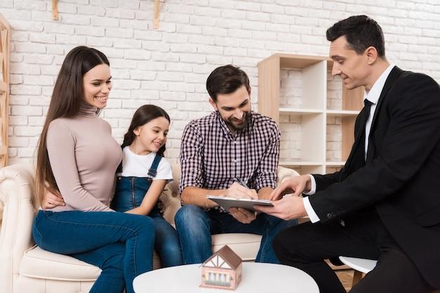 Familie unterzeichnet geschäftspartnervereinbarung, um haus zu kaufen