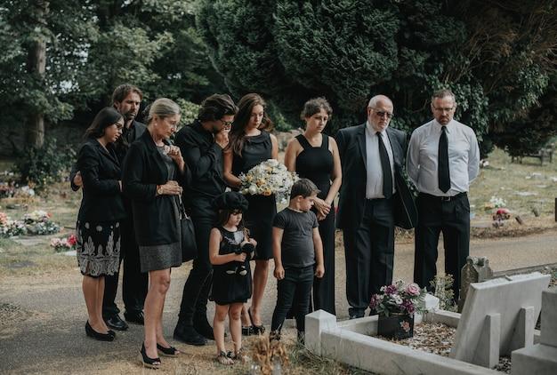 Familie verabschiedet sich auf dem friedhof