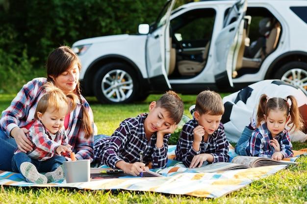 Familie verbringt zeit zusammen. mutter mit vier kindern im freien in picknickdecke gegen ihren amerikanischen geländewagen.