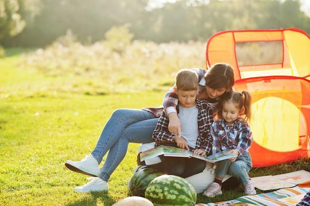 Familie verbringt zeit zusammen. mutter mit zwei kindern liest buch im freien in picknickdecke und kinderzelt.