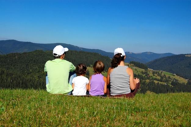 Familie von eltern und zwei kindern, die auf dem gras sitzen und den schönen blick auf die berge betrachten
