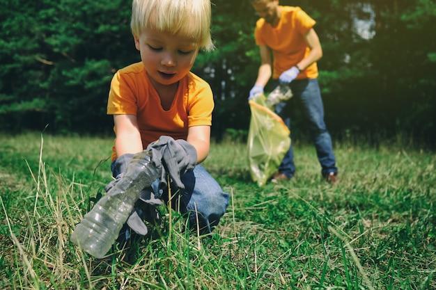 Familie von freiwilligen mit den kindern, die abfall im park sammeln. umgebungskonzept speichern. kleiner junge und sein vater räumen den wald auf