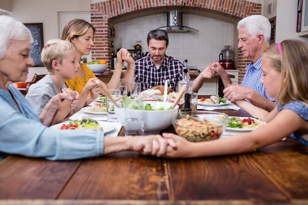 Familie von mehreren generationen, die bevor mahlzeit betet