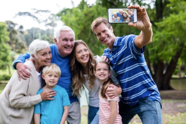 Familie von mehreren generationen, die ein selfie im park nimmt
