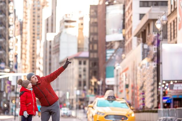Familie von vater und kind auf dem times square während ihres urlaubs in new york city
