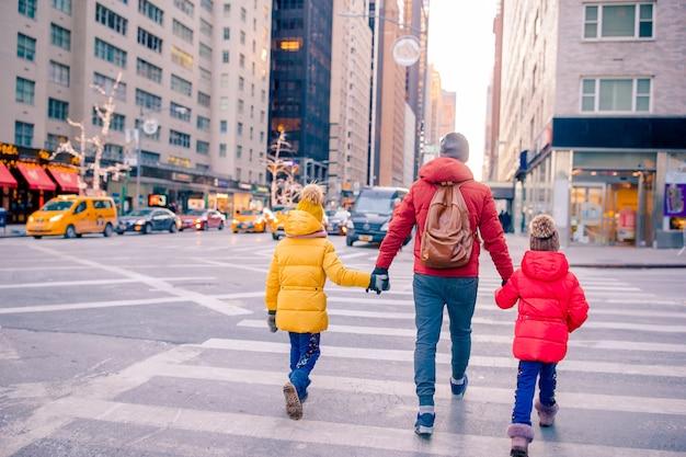Familie von vater und kleinen kindern am times square während ihres urlaubs in new york city