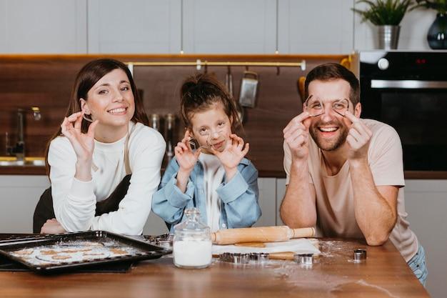 Familie von vater und mutter mit tochter, die in der küche zu hause kocht