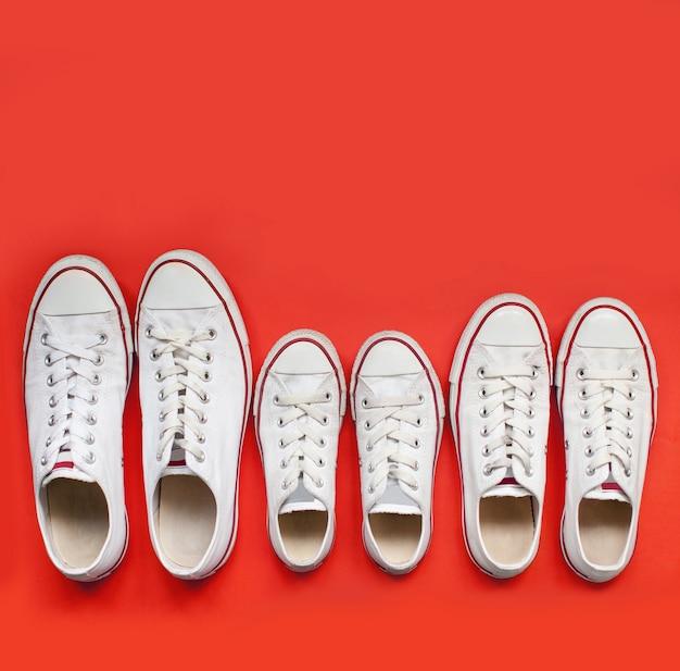 Familie von weißen schuhen. mamas, papas, kinderturnschuhe stehen auf rotem hintergrund