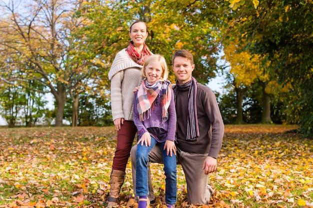 Familie vor bunten bäumen im herbst oder im fall