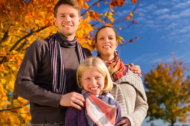 Familie vor bunten bäumen im herbst oder