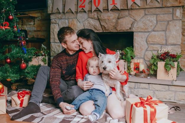 Familie vor dem kamin sitzen mit ihrem baby und ihrem hund und einem weihnachtsbaum