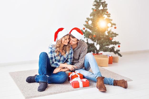 Familie, weihnachten, winterferien und menschenkonzept - glückliches paar, das sich zu hause in der nähe des weihnachtsbaums umarmt.