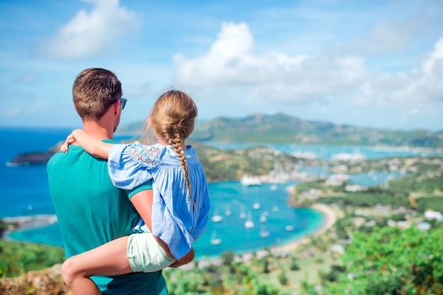 Familie, welche die ansicht des malerischen englischen hafens in antigua im karibischen meer genießt