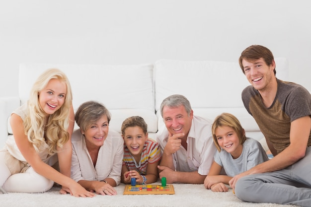 Familie, welche die kamera mit brettspielen betrachtet