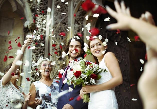 Familie wirft rosenblätter an der frisch vermählten braut und am bräutigam