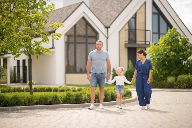 Familie zu fuß. stilvolle glückliche eltern und tochter, die am wochenende in der hüttenstadt spazieren gehen