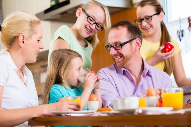 Familie zu hause, die in der küche frühstückt
