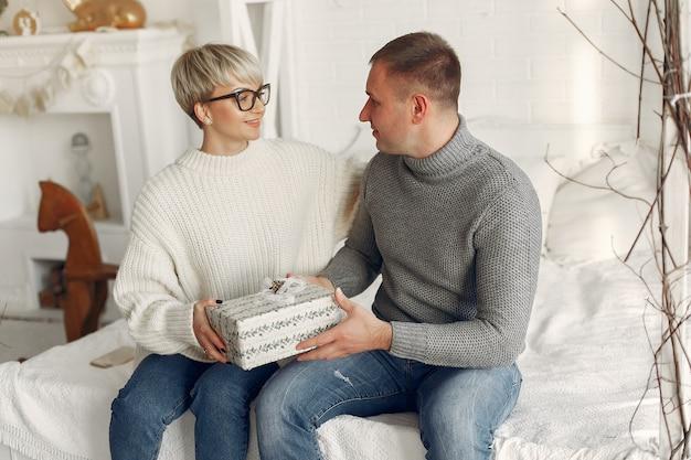 Familie zu hause. paar in der nähe von weihnachtsdekorationen. frau in einem grauen pullover.