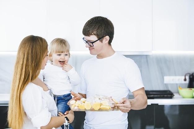 Familie zusammen glücklich jung schön mit einem kleinen kind, das abendessen in der küche zu hause vorbereitet