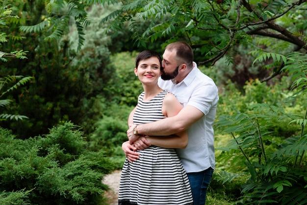 Familie zusammen im sommerpark im freien. frau ist schwanger