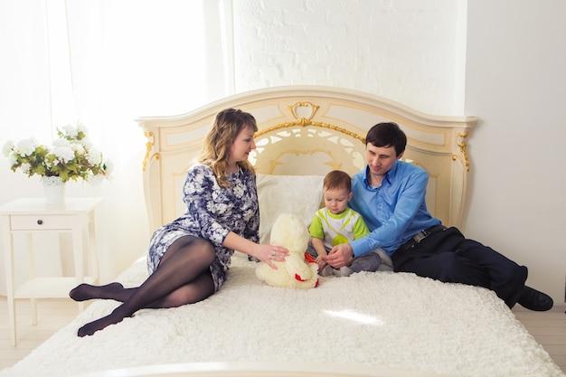 Familien-, eltern- und kinderkonzept - glückliche mutter, vater und sohn, die zusammen mit teddybären auf dem bett im schlafzimmer zu hause spielen.