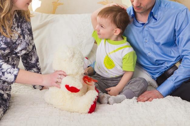 Familien-, elternschafts- und kinderkonzept - nahaufnahme von glücklicher mutter, vater und sohn, die zusammen mit teddybären auf dem bett im schlafzimmer zu hause spielen.