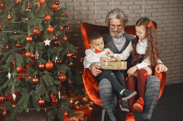 Familien-, feiertags-, generationen-, weihnachts- und personenkonzept. kinder in einem zu weihnachten dekorierten raum.