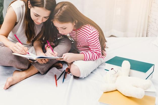 Familien-glückliche mutter- und tochterzeichnung mit bunten bleistiften auf buch im schlafzimmer