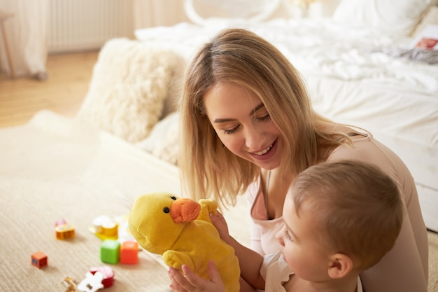 Familien-, kindheits-, mutterschafts- und prenting-konzept. nette szene der blonden jungen mutter, die auf boden im schlafzimmer mit ihrem entzückenden kleinen sohn sitzt, umgeben von spielzeugen, die mit ausgestopfter gelber ente spielen
