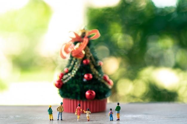 Familien-miniaturleute, die auf weihnachtsbaum stehen feiern sie weihnachten
