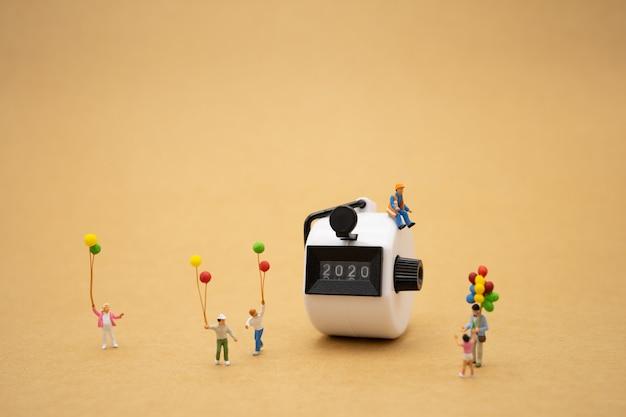Familien-miniaturleute, die mit 2020 guten rutsch ins neue jahr stehen