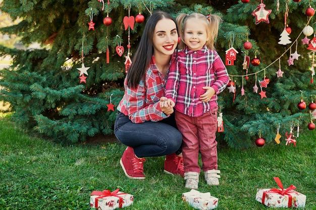 Familien-neujahrsfotosession der mutter und der tochter im juli nahe dem weihnachtsbaum mit geschenken im park
