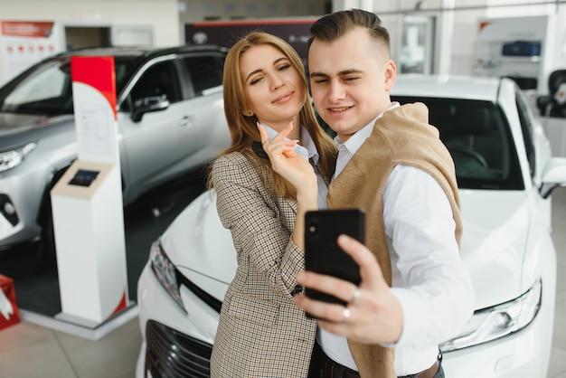 Familien-selfie im autohaus. glückliches junges paar wählt und kauft ein neues auto für die familie.
