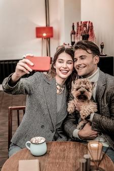 Familien-selfie. junges paar, das lustiges selfie mit ihrem hund macht