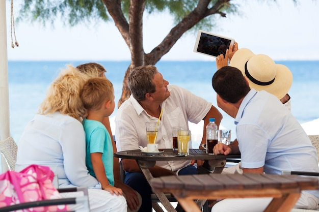 Familien-selfie mit tablet-pc café im im freien auf erholungsort