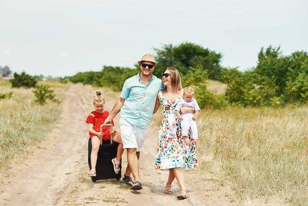 Familien-, sommerferien-, adoptions- und personenkonzept - glücklicher mann, frau und töchter in der sonnenbrille, mit koffern, die spaß über blauem himmel haben