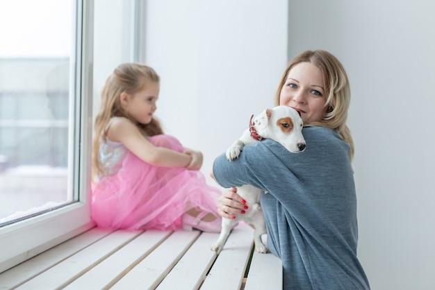 Familien- und haustierkonzept - mutter und tochter, die zu hause mit jack-russell-terrier-hund spielen.