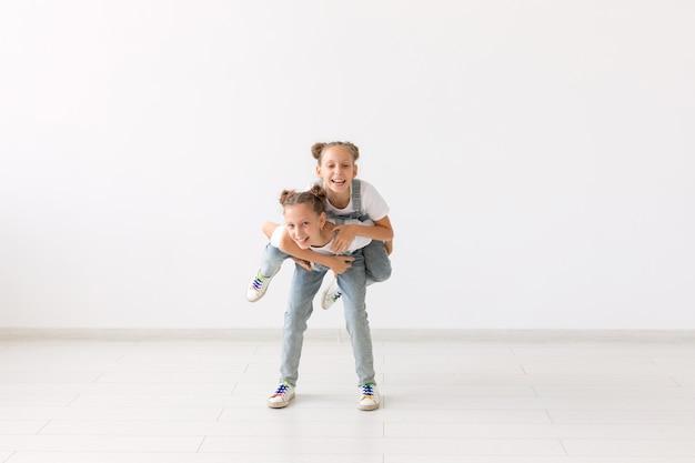 Familien- und liebeskonzept - glückliches zwillingsmädchen, das ihrer lachenden schwester eine huckepackfahrt gibt.