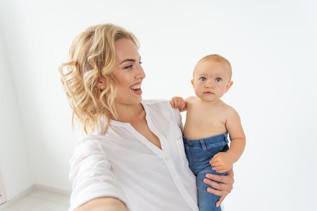 Familien- und mutterschaftskonzept glückliche junge blonde mutter mit kleinem baby, das selfie nimmt