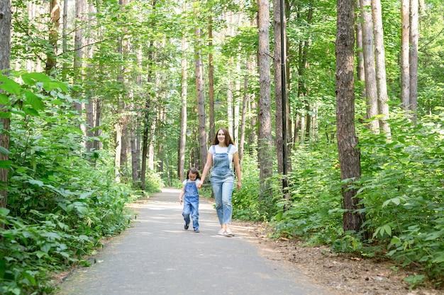 Familien- und naturkonzeptporträt des schönen frauen- und kindermädchens, das im sommerpark geht