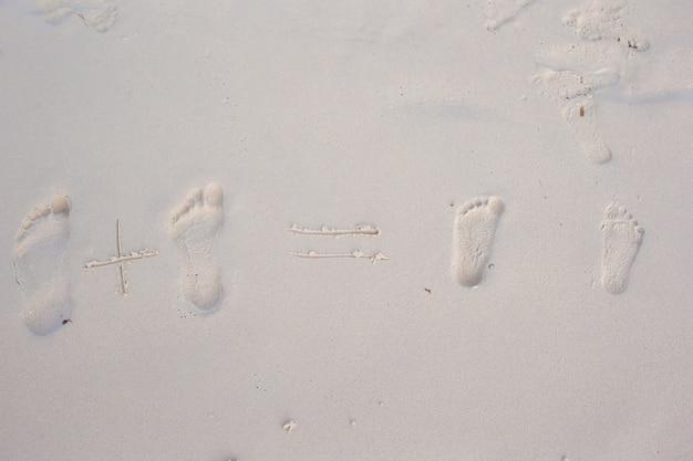 Familienabdrücke auf dem weißen sandstrand